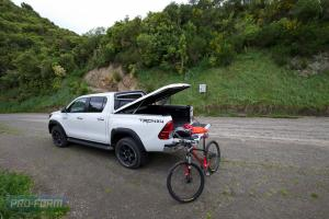 orange Toyota Hilux with OEM bar and Sportlid for Tango Tonneau cover White