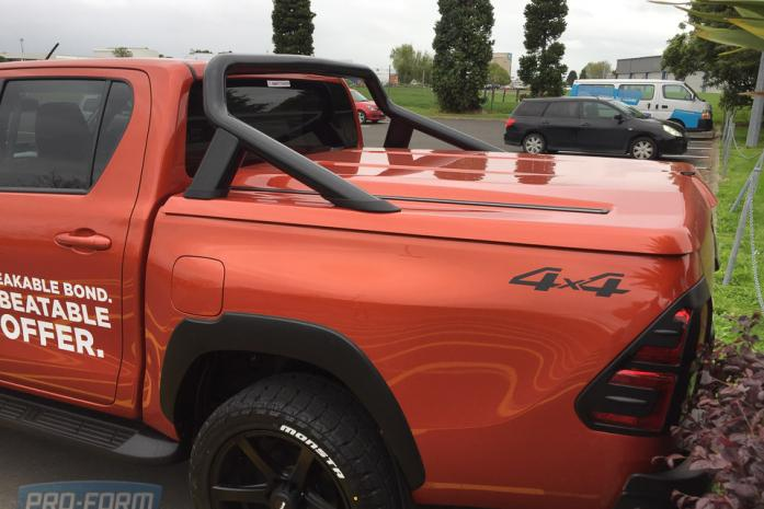 orange Toyota Hilux with OEM bar and Sportlid for Tango Tonneau cover